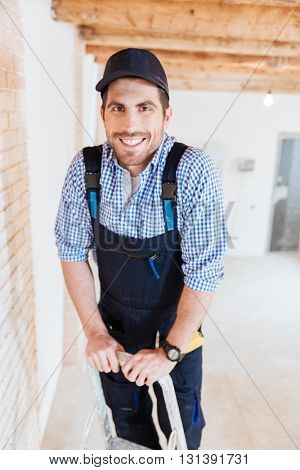 Smilling handsome builder standing on the ladder at the working space indoors