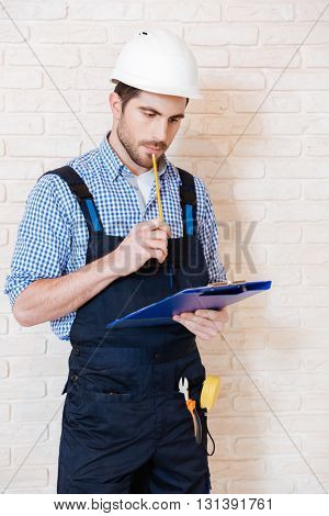 Pensive young construction worker thinking about something using clipboard while working indoors