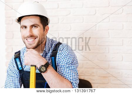 Close-up portrait of a cheerful young builder in a hardhat with a level