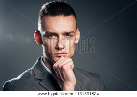 Pensive businessman looking at camera over gray background