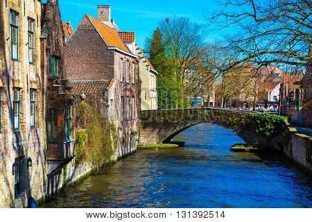 Bruges, Belgium - April 10, 2016: Scenic cityscape with houses,  bridge and Green canal, Groenerei in Bruges, Belgium