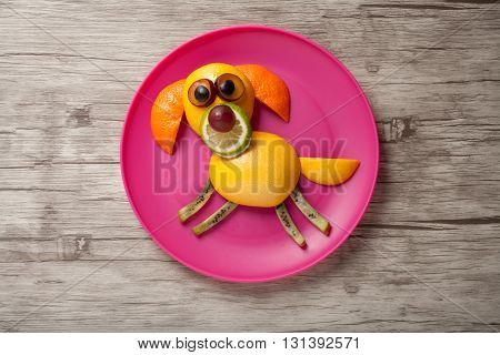Dog made of fruits on plate and wooden desk