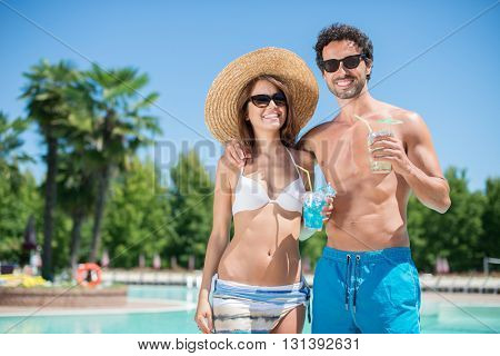 Smiling couple holding a cocktail near the pool