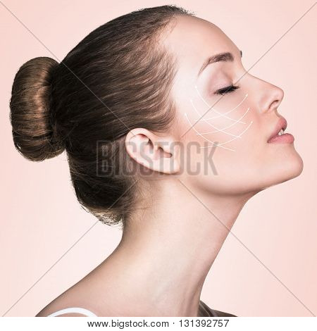Close-up portrait of young, beautiful and healthy woman with arrows on her face. Spa, surgery, face lifting and make-up concept
