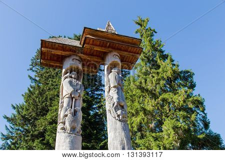 commemorative pillars at Synevir Lake in the Carpathian Mountains on a background of blue sky and fir trees with a picture of a guy and a girl