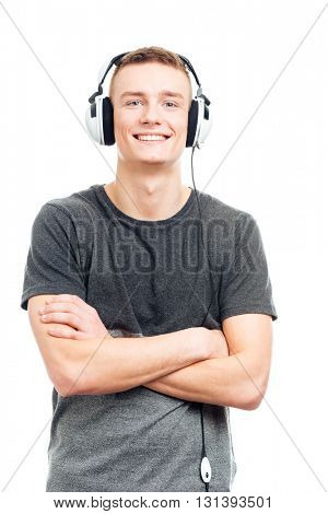 Happy casual man standing with arms folded and listening music in headphones isolated on a white background