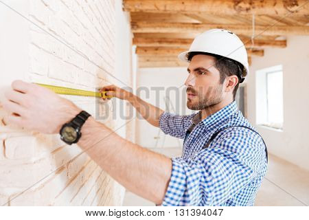Close-up portrait of a pensive builder measuring wall using yellow type indoors
