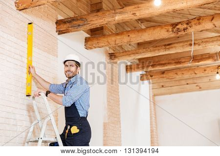 Smilling handsome builder using level and standing in the ladder at the working area indoors