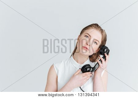 Young woman with fresh sking holding retro phone tube and looking at camera isolated on a white background