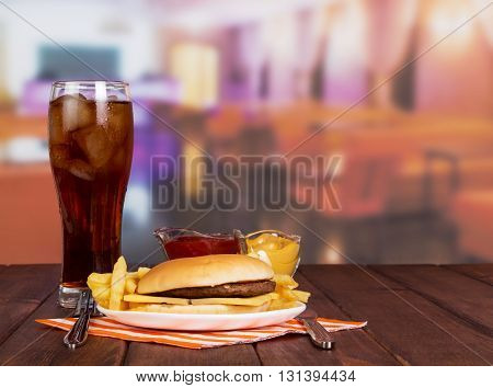 Hamburger, french fries, glass of cola, sauces and cutlery in the background of the hall cafe.