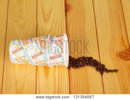 The empty paper cups and coffee beans on a background of light wood.