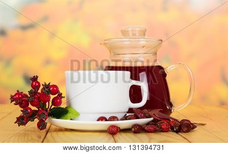 Jug and cup of tea rosehip berries on a background of autumn leaves.