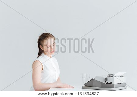 Relaxed woman sitting at the table with retro machine isolated on a white background