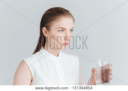 Beauty portrait of a thoughtful woman holding glass with water isolated on a white background