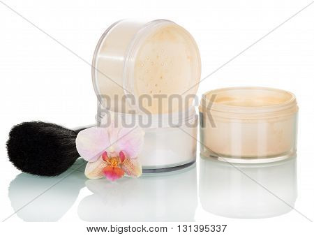 Cosmetic brush, banks face powder and orchid flower isolated on white background.
