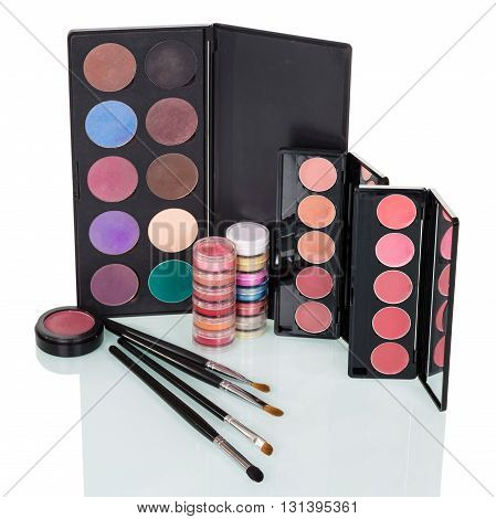 Cosmetics Set: eye shadow, blush, lip gloss and brushes for makeup isolated on white background.