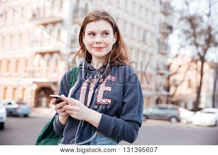 Happy cute young woman in sweatshirt using earphones and listening to music from cell phone in the city