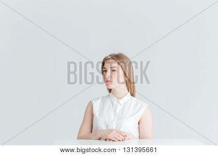 Attractive blonde woman sitting at the table isolated on a white background and looking away