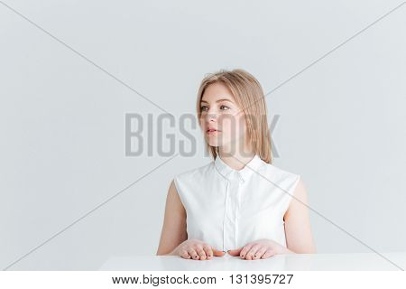 Beautiful blonde woman sitting at the table and looking away isolated on a white background