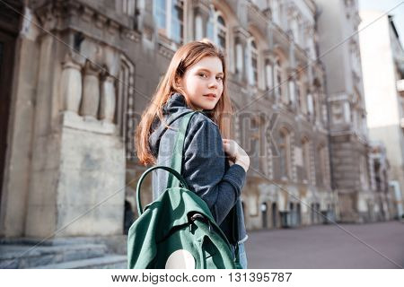 Pretty young woman with green backpack walking around old city