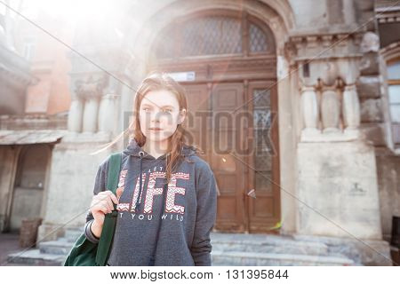 Closeup of cute young woman standing near the doors of house in old city