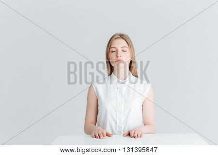 Beauty portrait of relaxed woman with closed eyes sitting at the table isolated on a white background
