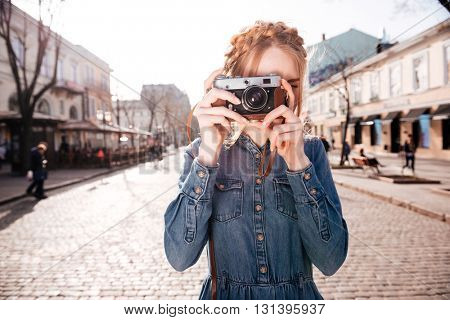 Attractive blonde young woman taking pictures with old vintage camera on the street