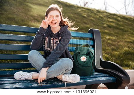 Funny playful young woman winking and showing peace sign sitting on the bench