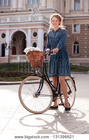 Portrait of beautiful young woman standing with bicycle in the city
