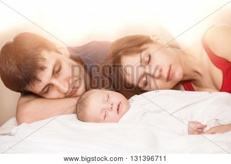 Sleeping baby with mom and dad. Bright daylight shining from the window