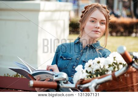 Beautiful blonde young woman with bicycle reading magazine on the bench outdoors