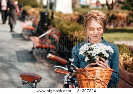 Charming young woman with bicycle sitting on bench and holding bouquet of flowers