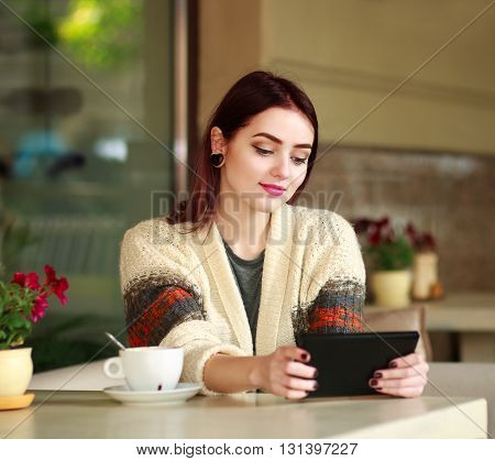 Nice girl in a summer cafe looking at tablet