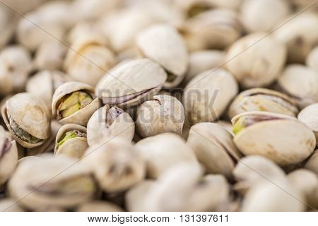 Whole Pistachios on wood as detailed close-up shot (selective focus)