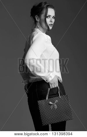 Woman With Shopping Bag Looking Back Against Grey Background