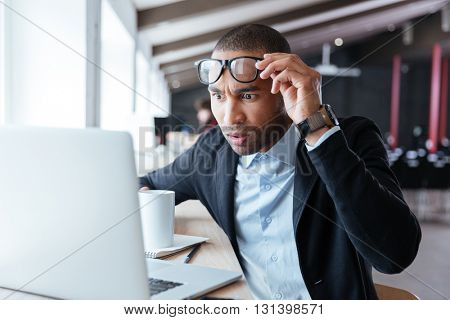 Businessman receiving negative news, touching his glasses, being mad, upset and surprised in front of laptop