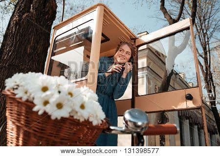 Smiling beautiful young woman using telephone box on the street