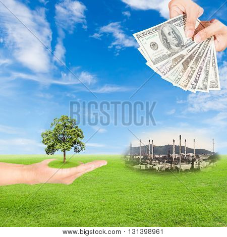 Carbon credits concepthand holding tree and US Dollars banknote with oil refinery plant against green field and blue sky background
