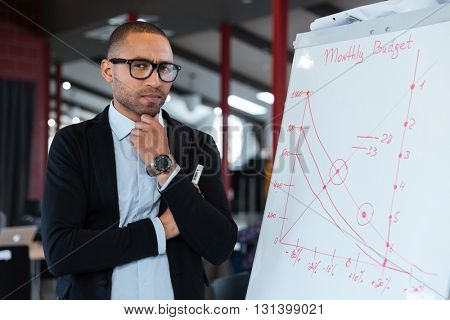 Pensive businessman thinking about something at the flipchart in the office