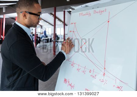 Handsome young businessman writing on a flipchart at the office
