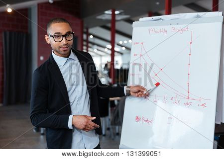 Businessman pointing and presenting something on the flipchart