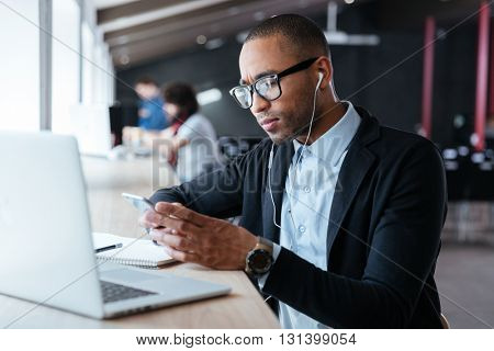 Concentrated handsome young businessman received bad news on the the smartphone during work process
