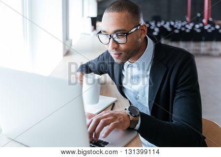 Young stylish businessman working using laptop computer in the office
