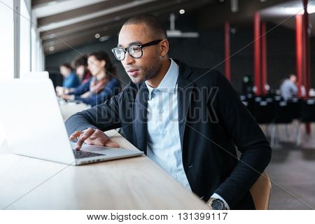 Portrait of a businessman working using laptop at the office