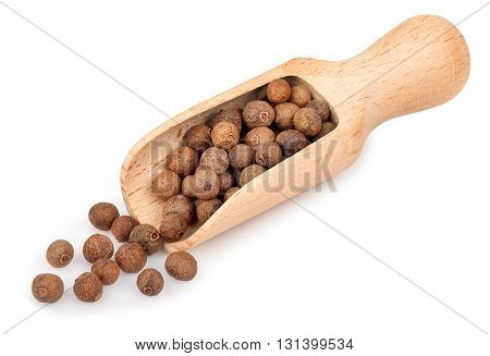 pimento peppercorns in wooden scoop isolated on white background. Whole allspice berries in wooden scoop. Myrtle pepper. Jamaica pepper. Spice of peppers in a wooden scoop