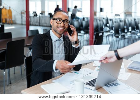 Smiling bisnessman giving papers to someone in office