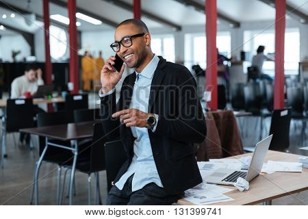 Happy businessman talking on the smartphone in the office