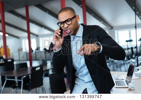 Furious angry businessman talking on the smartphone in the office
