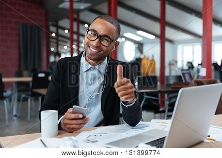Stylish young businessman showing okay sign and holding smartphone at the laptop