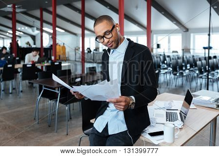 Young smart businessman is looking through documents in the office